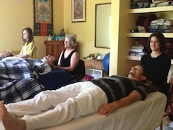 Students learning at a massage table